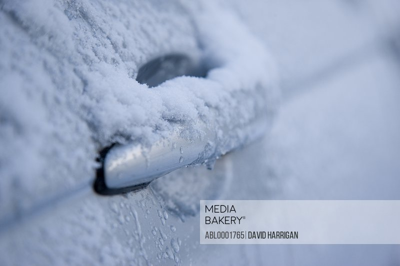 Car door handle covered in snow
