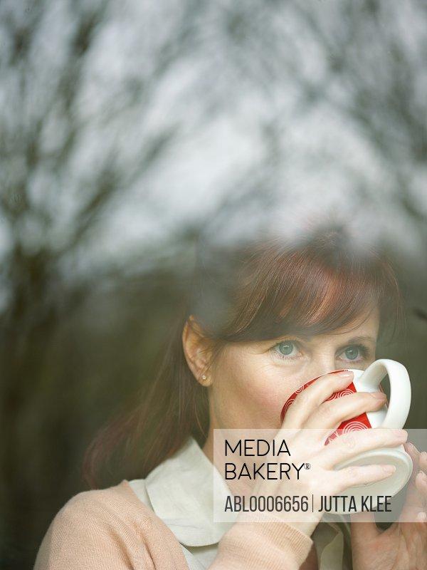 Woman Drinking Coffee behind Window