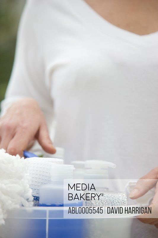 Close up of a woman holding a plastic container filled with cleaning products - headless