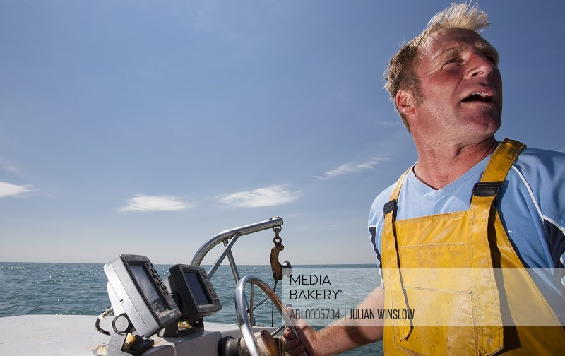 Close up of a fisherman driving a boat