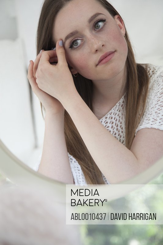 Teenage Girl Looking in Mirror Checking Eye Makeup