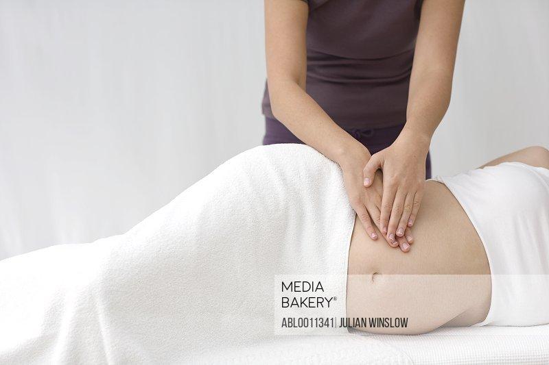 Massage therapist's hands massaging pregnant woman stomach