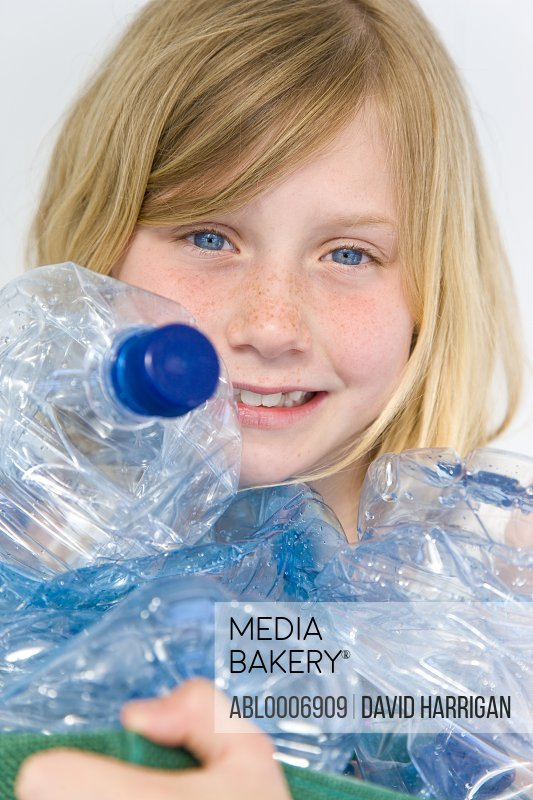 Smiling Girl Holding Crushed Plastic Bottles