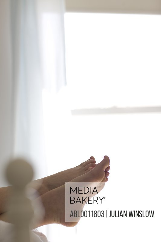 Woman feet overhanging from end of bed