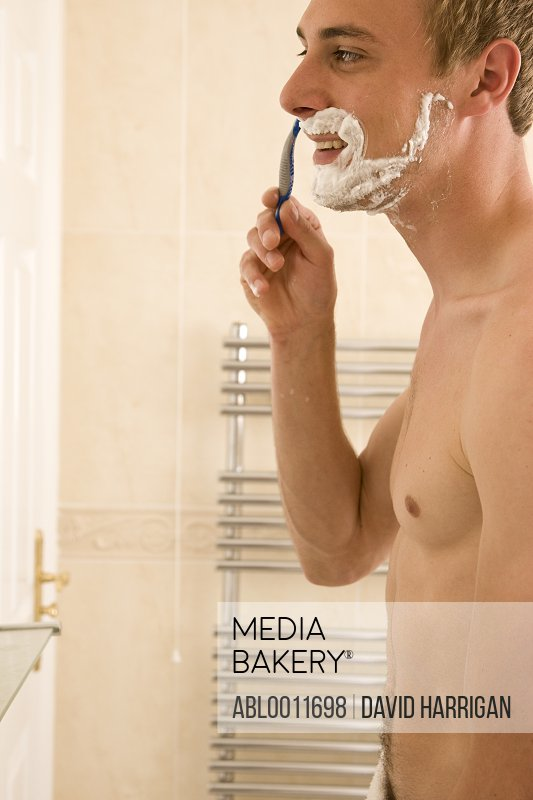 Portrait of a man shaving and holding razor