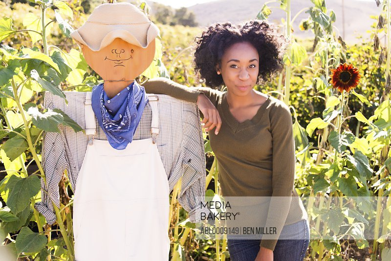 African American Woman in Sunflower Field Posing with Scarecrow