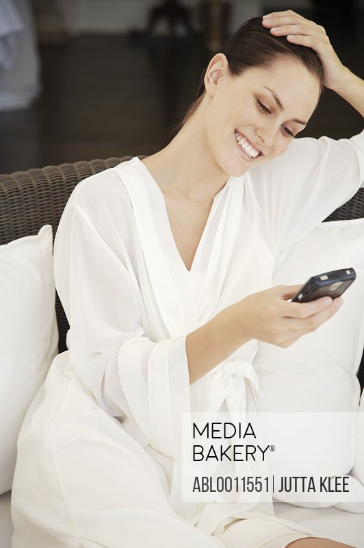 Portrait of a woman smiling and text messaging on cell phone