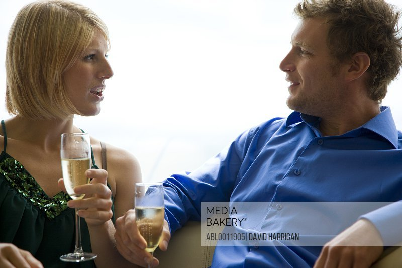 Young couple sitting and holding champagne glasses