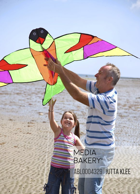 Portrait of father and daughter flying a kite
