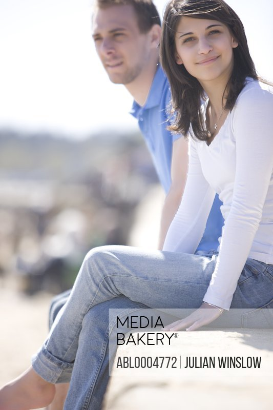 Young couple sitting on top of a wall