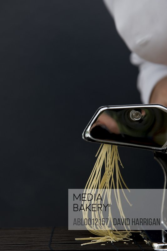 Close up of a chef hand turning the handle of a pasta maker with tagliolini coming out