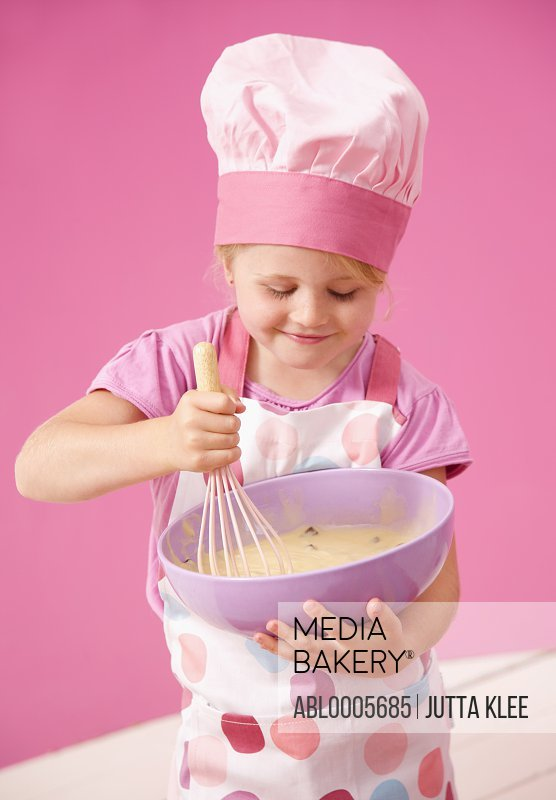 Young girl holding a baking bowl and whisking cake mix