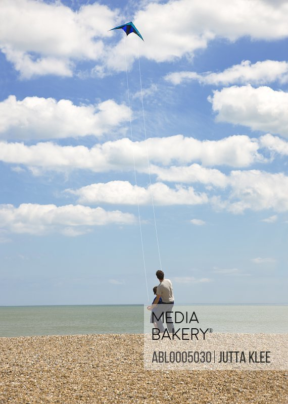 Back view of father and son standing on a beach flying a kite