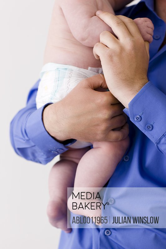 Man holding newborn baby in his arms