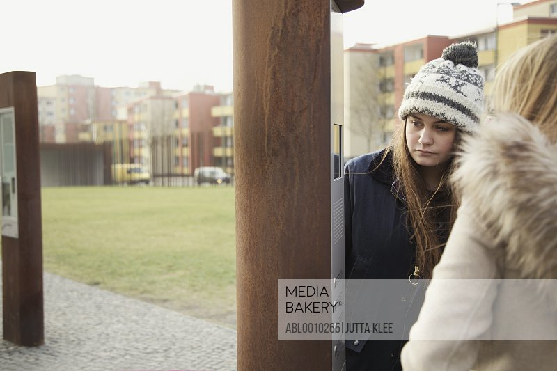 Teenage Girls in front of Information Terminal at the Berlin Wall Memorial, Berlin, Germany