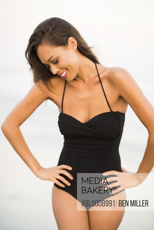 Woman Wearing Black Swimsuit with Hands on Hips