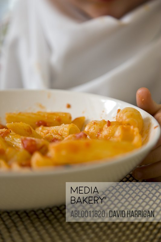 Close up of bowl of pasta with young boy hand