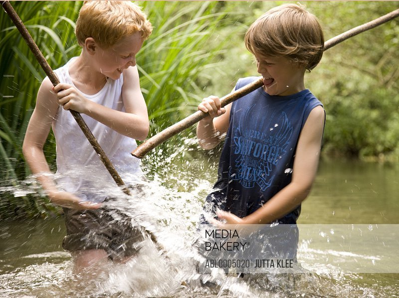 Two young boy playing in a river holding wooden sticks and splashing water to each other