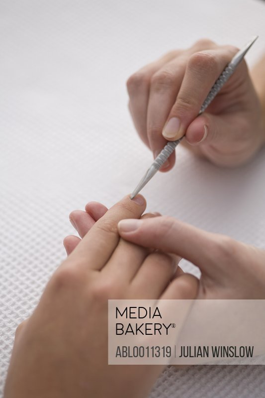 Close up of manicurist's hand pushing woman's cuticles with cuticle pusher