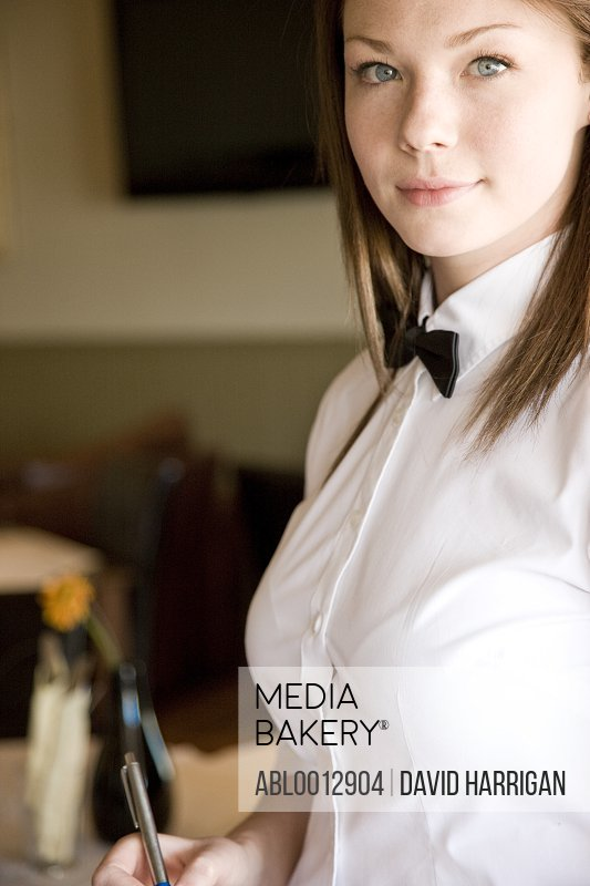 Portrait of a waitress holding a pen