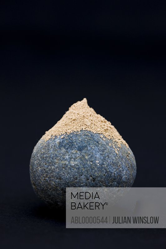 Close up of spherical gray stone with sand on top