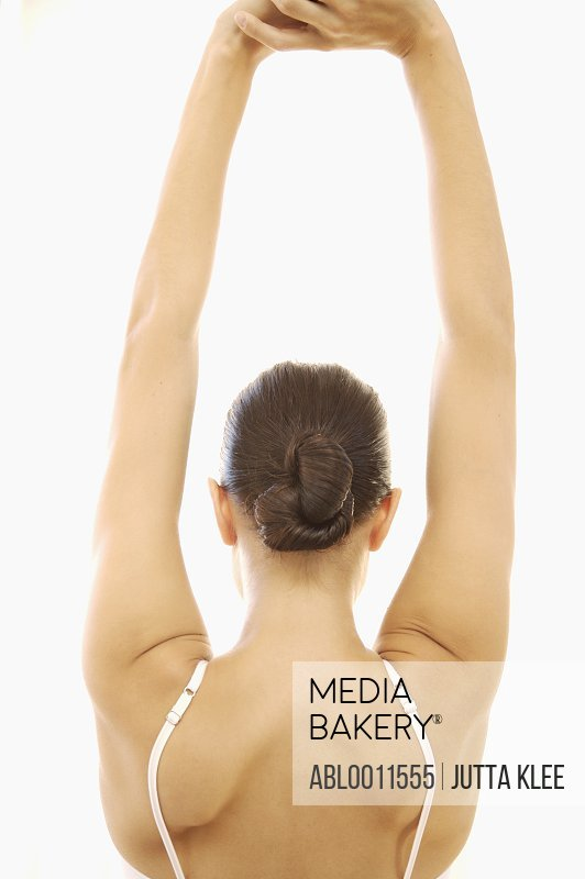 Back of young woman stretching arms over her head