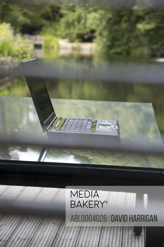 Laptop computer on glass table