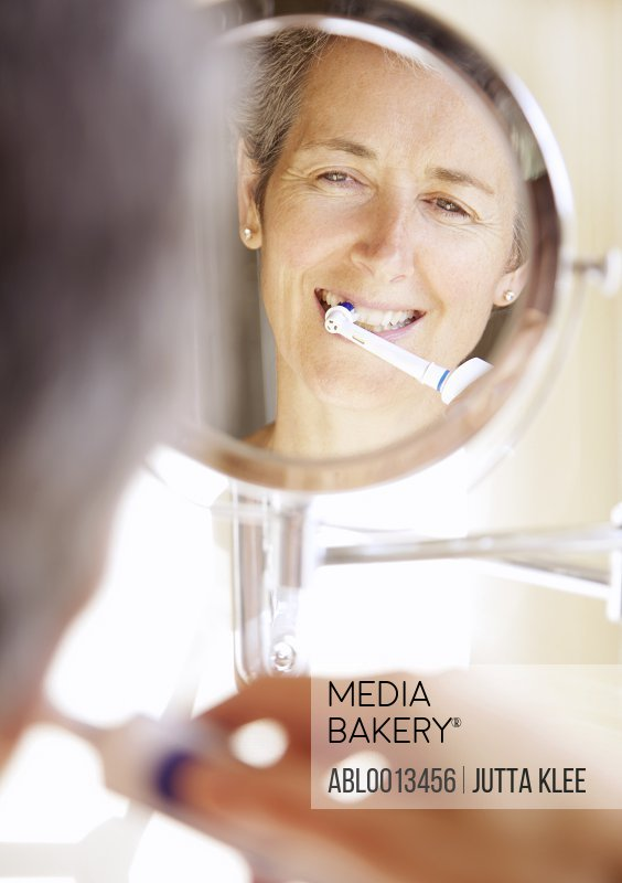 Woman Looking into Round Mirror Brushing Teeth