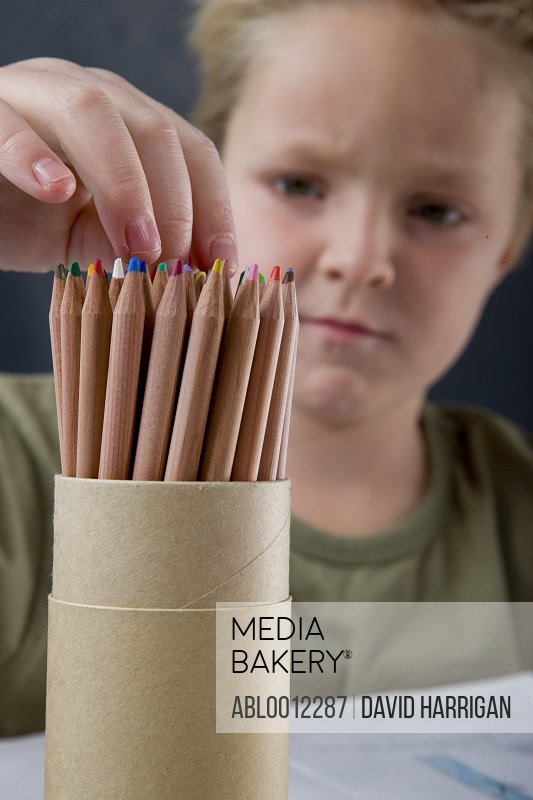 Boy selecting coloring pencil from container