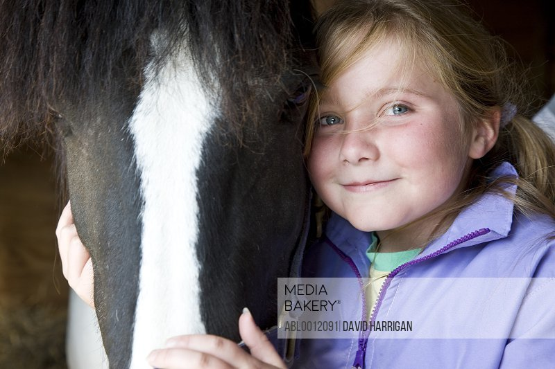Young girl hugging a horse head