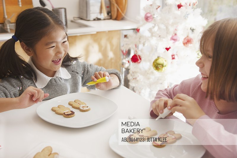 Two Young Girls Decorating Ginger bread man Biscuits