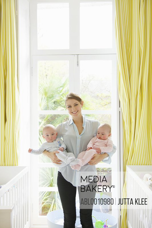 Smiling Mother Holding Twin Babies in Nursery
