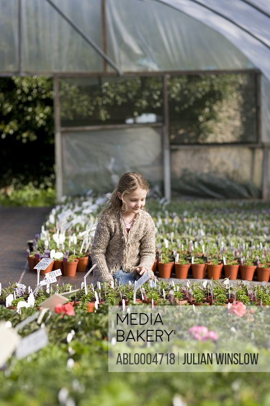 Young girl in a greenhouse kneeling and looking at plants