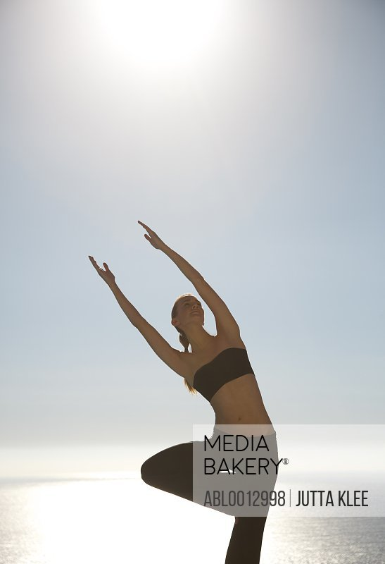 Young woman practicing yoga with ocean in the background