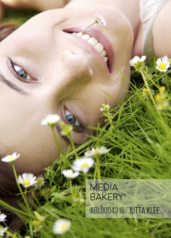Young woman laying on a field of flowers with daisy in her mouth