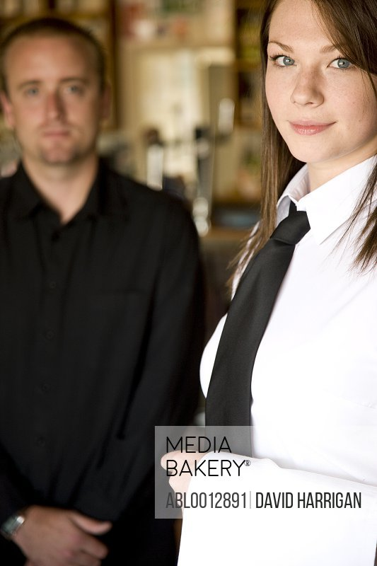 Portrait of a waitress standing next to a waiter