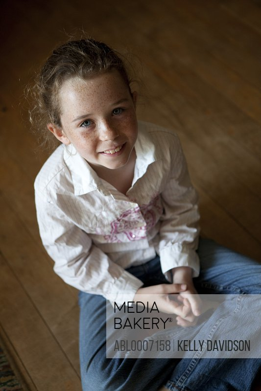 Smiling Girl Sitting on Wood Flooring