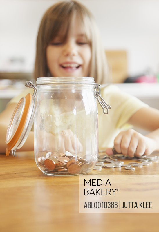 Smiling Young Girl Putting Coins in Jar