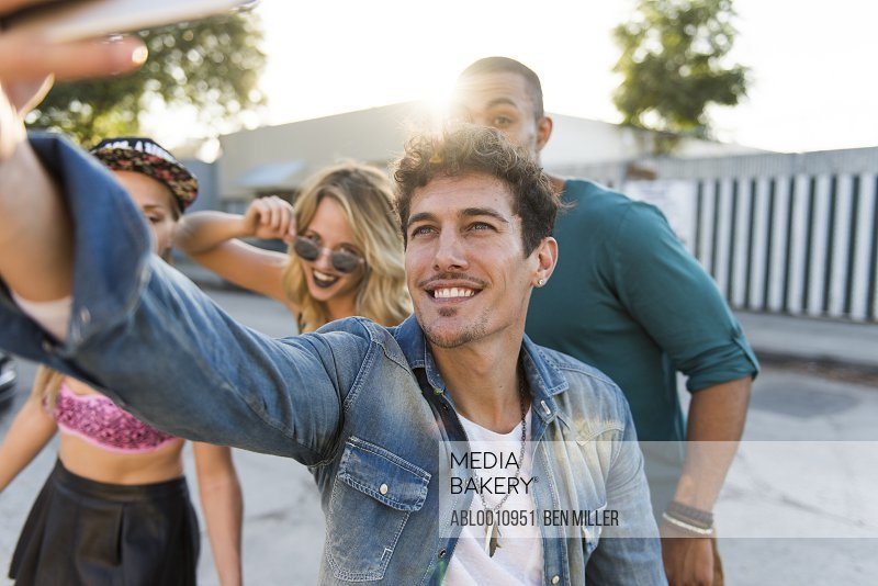 Smiling Man Taking a Group Selfie