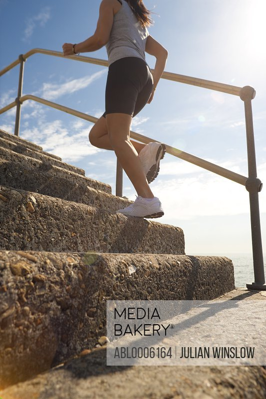 Profile of a woman running up steps, low angle view