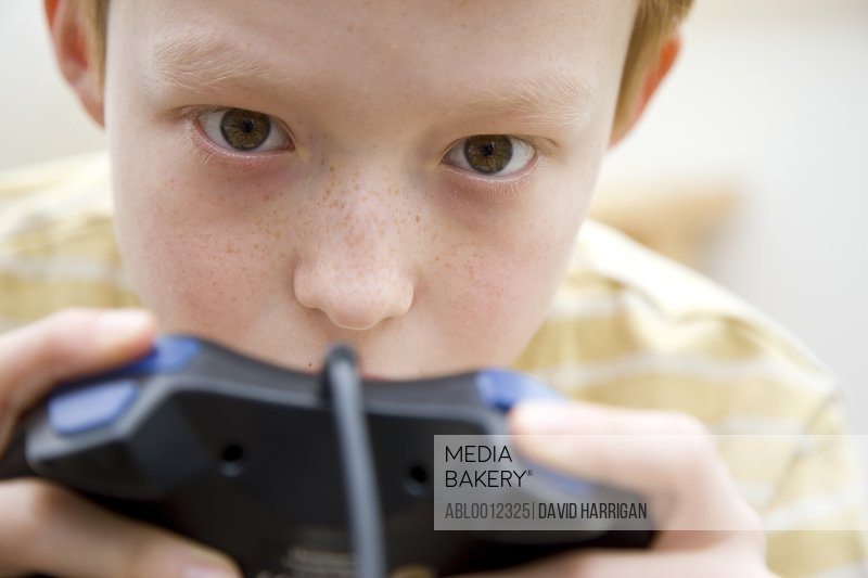 Close up of a boy holding a game controller