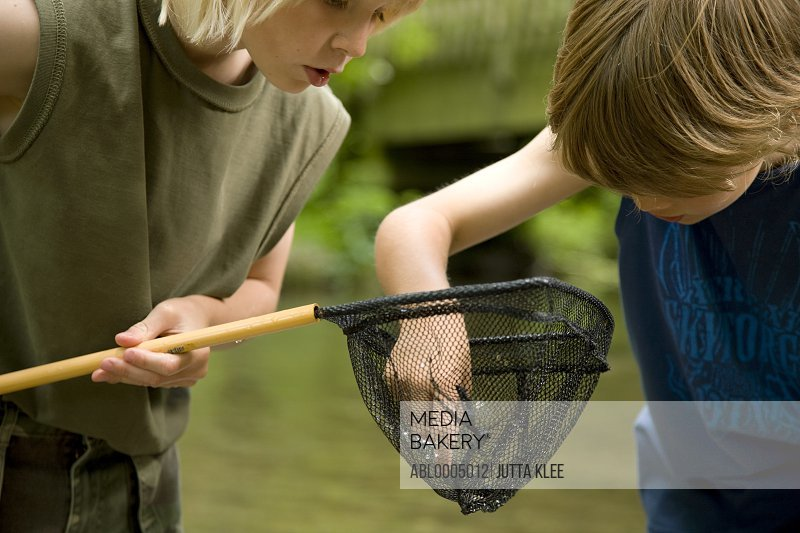 Two young boys inspecting  the content of a fishing net