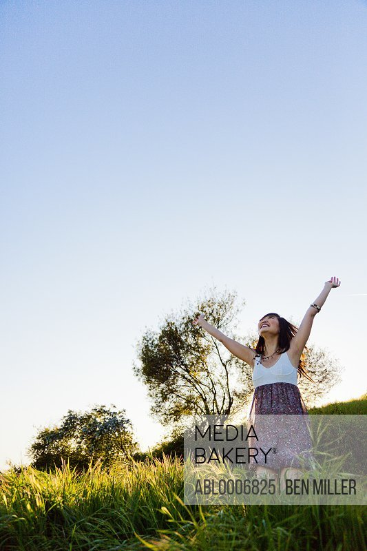 Young Woman with Arms Outstretched Outdoors