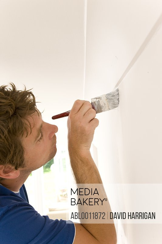 Close up of man painting under ceiling molding with a paint brush
