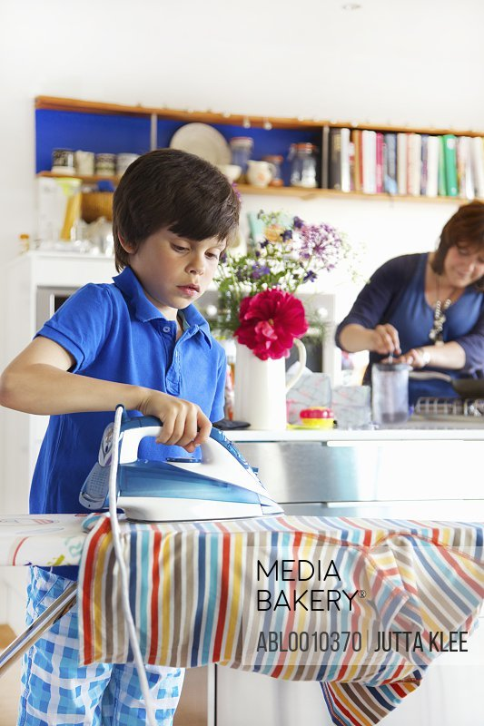 Young Boy Ironing in Kitchen, Mother in background