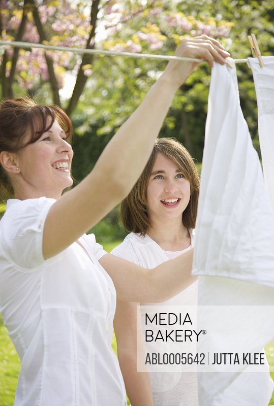 Smiling woman and teenage girl hanging linens on a clothesline