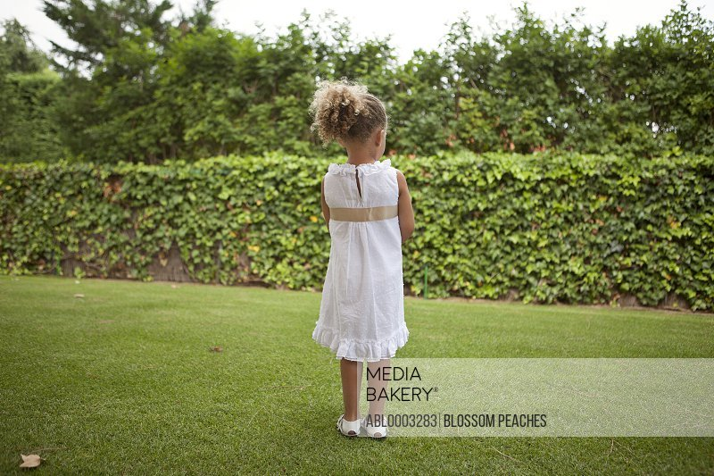 Back View of Young Girl Standing in Garden