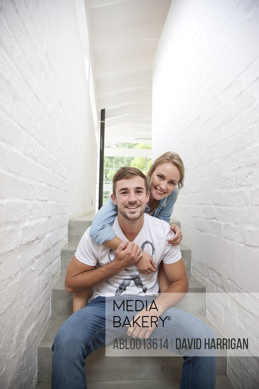 Smiling Young Couple Sitting on Stairs