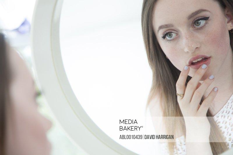Teenage Girl Looking in Mirror Touching her Lips