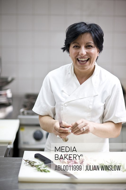 Woman chef peeling garlic with a knife and smiling
